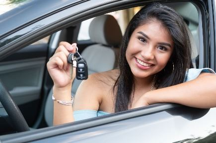 Teen driver holding keys in car